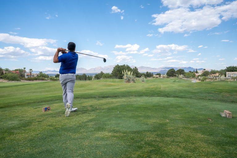 man hitting a golf ball on the green