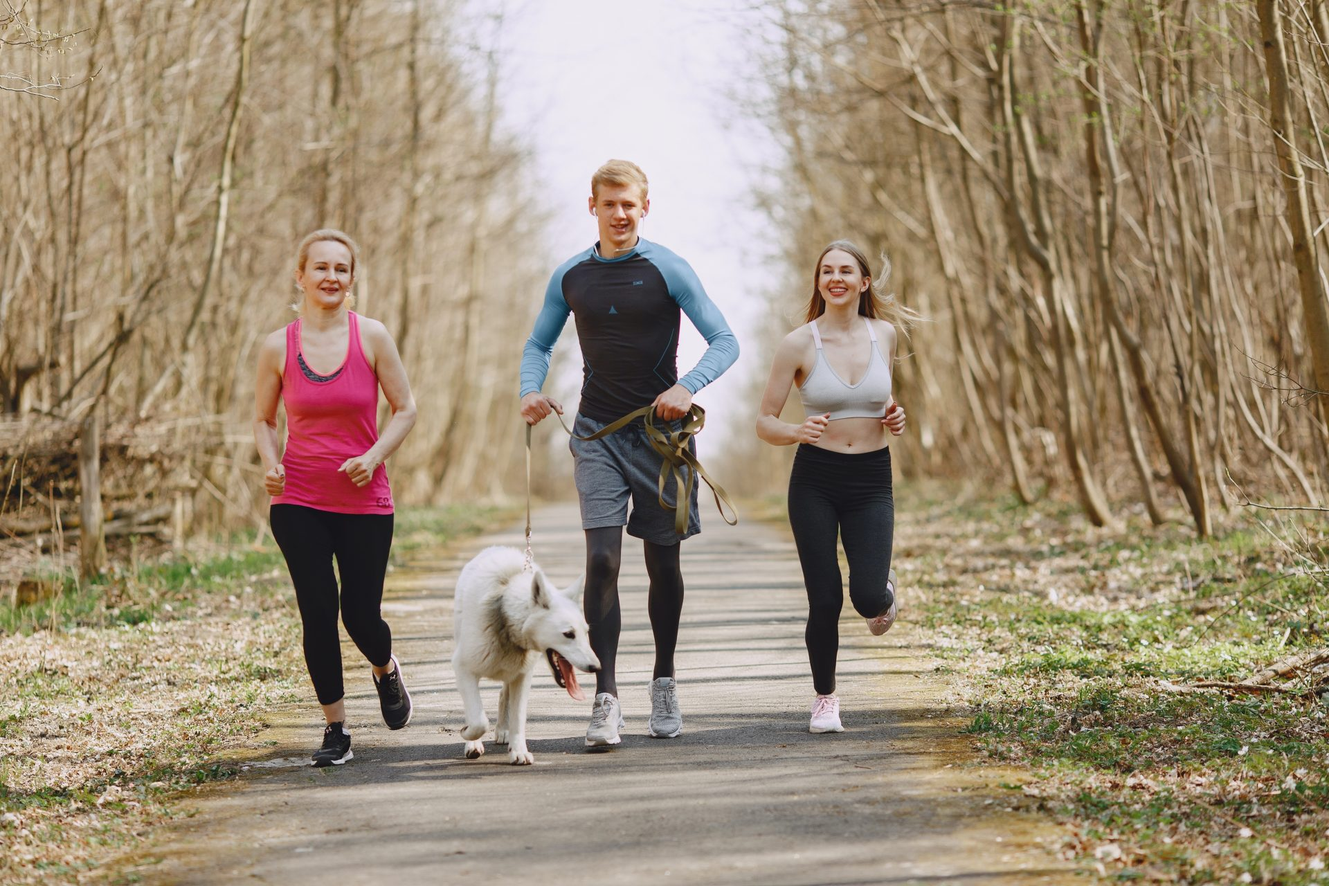 Photo Of Two Women And Man Jogging With Dog On Pavement