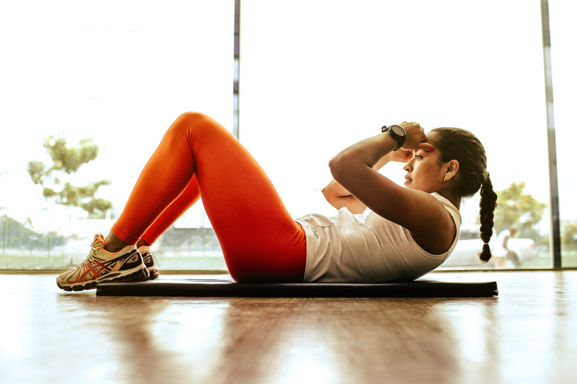 lady in red gym gear doing an abdominal crunch