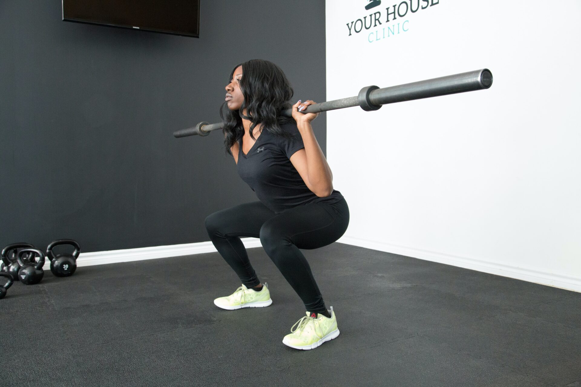 lady in a squat exercise with a bar