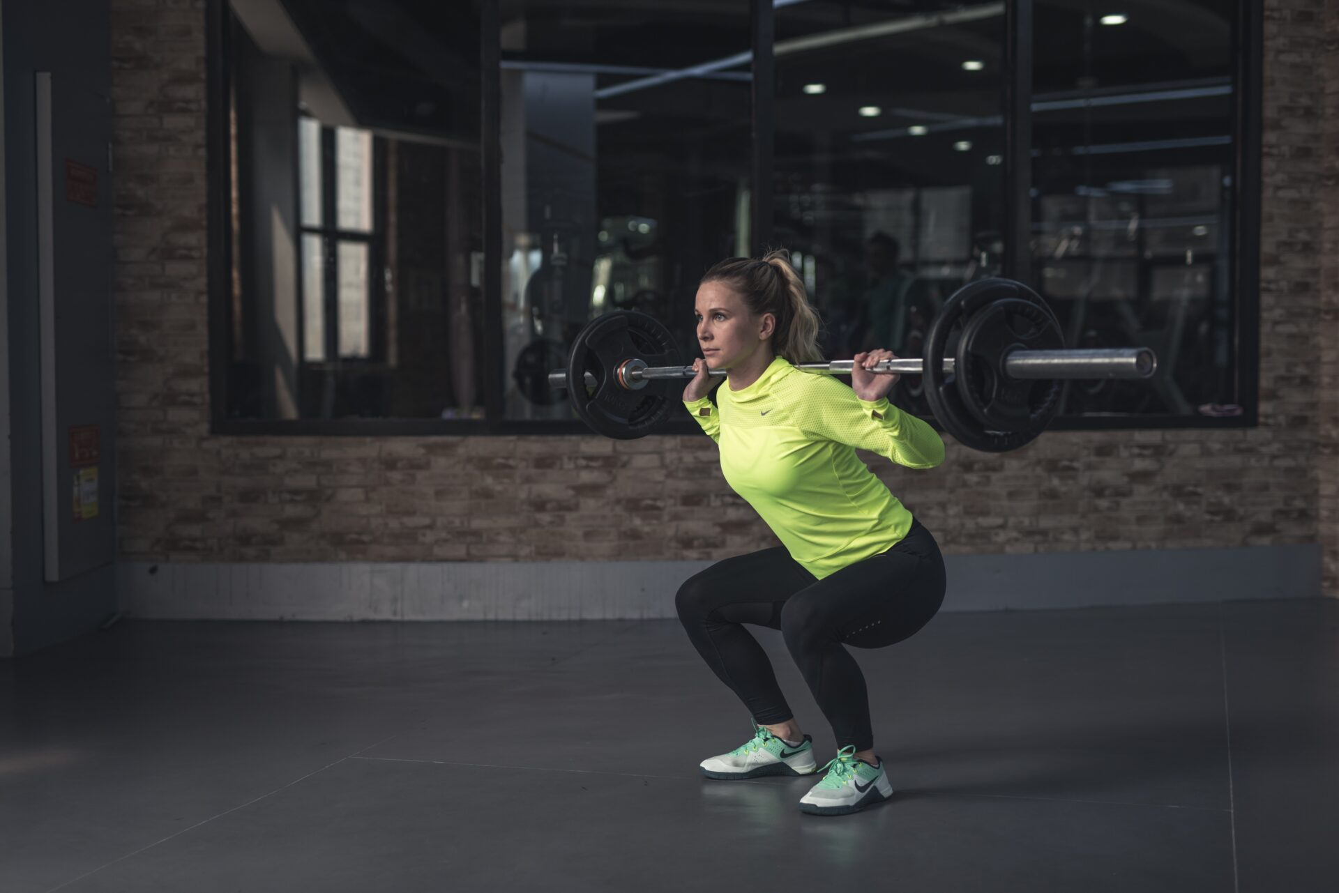 Woman Lifting Barbell in a squat position. Wearing a fluro yellow jumper and black leggings