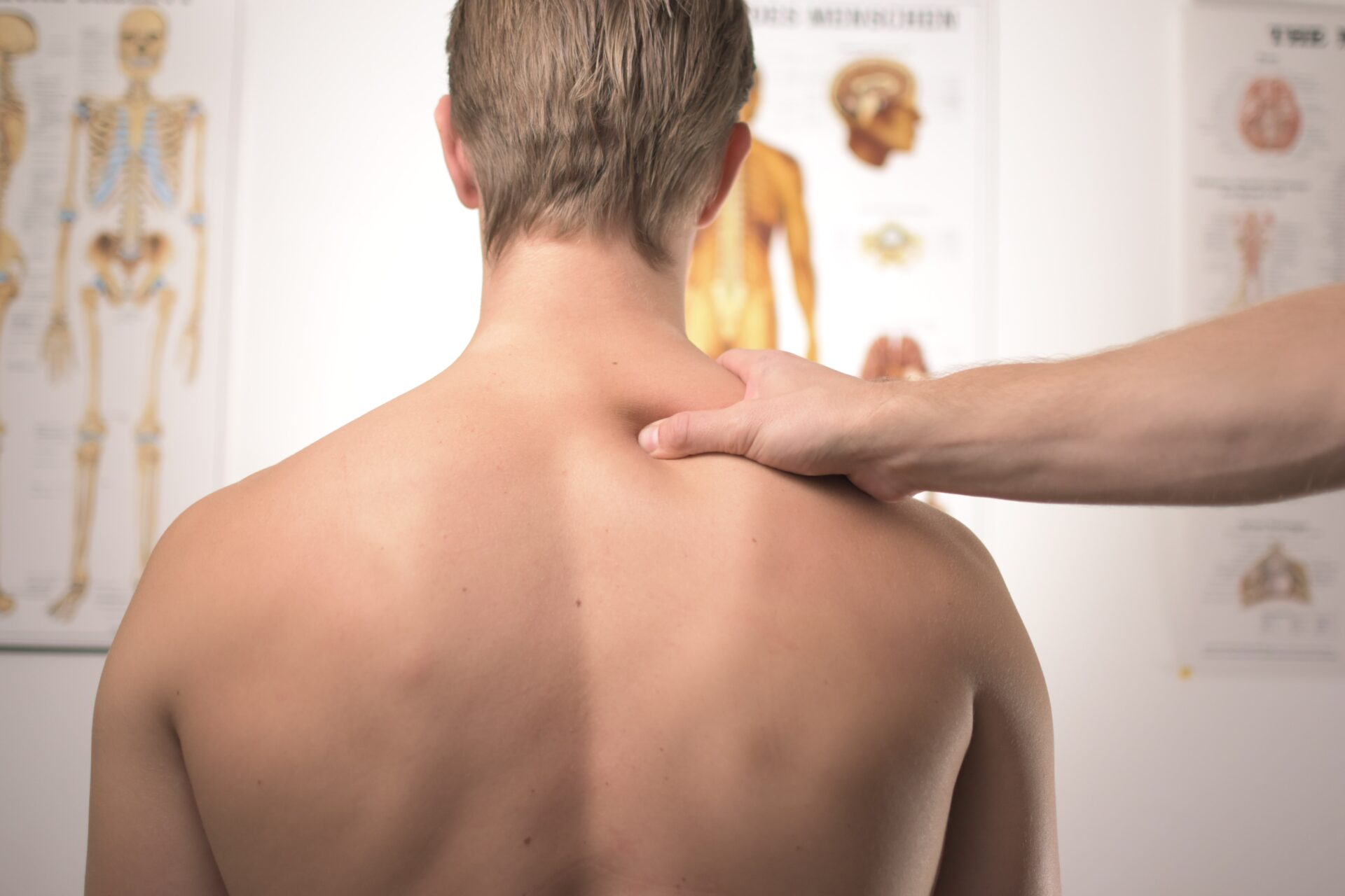 man facing backwards with a physio's hand on his left shoulder