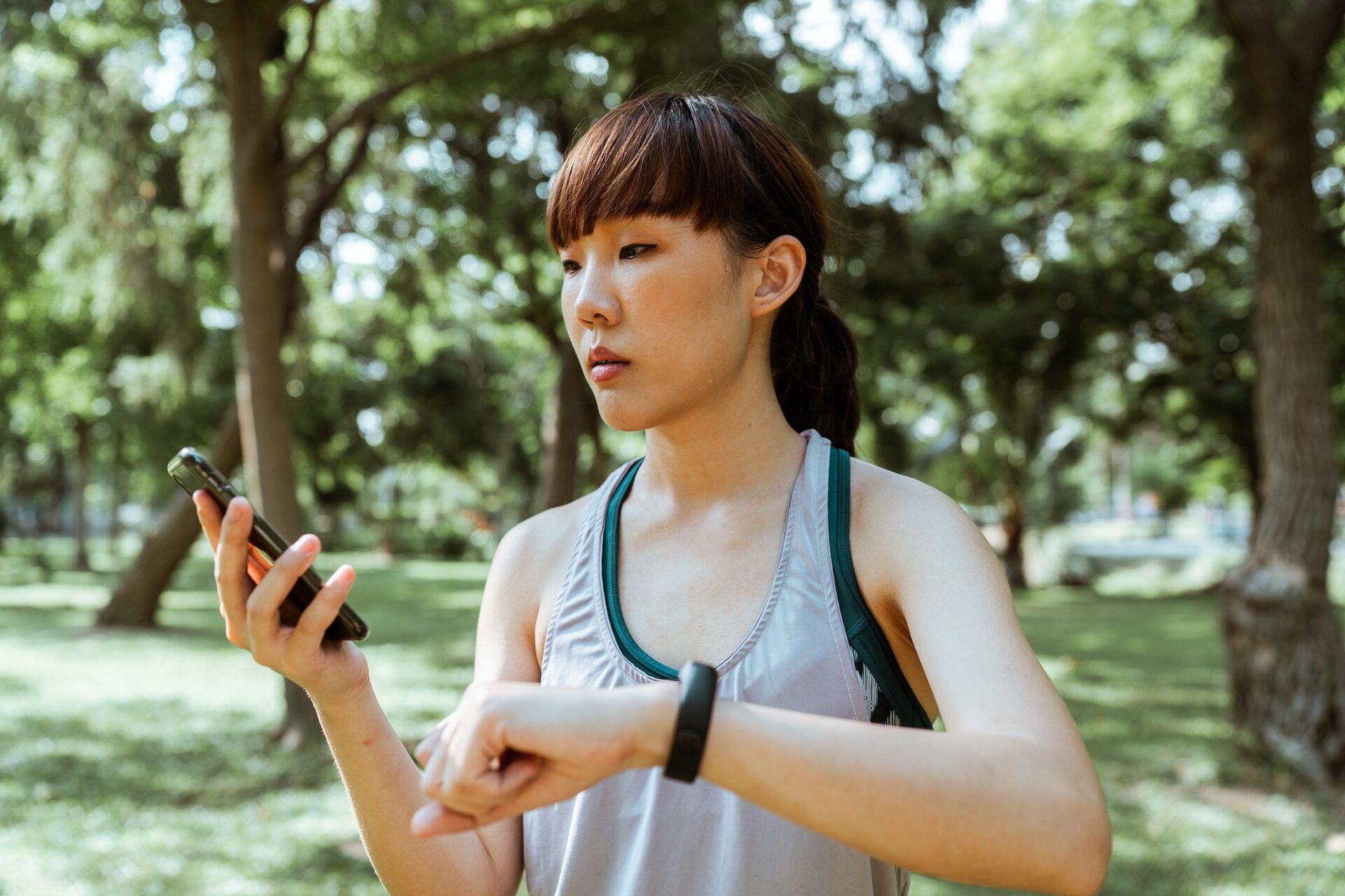 asian girl with a phone and a fitbit getting ready to exercise