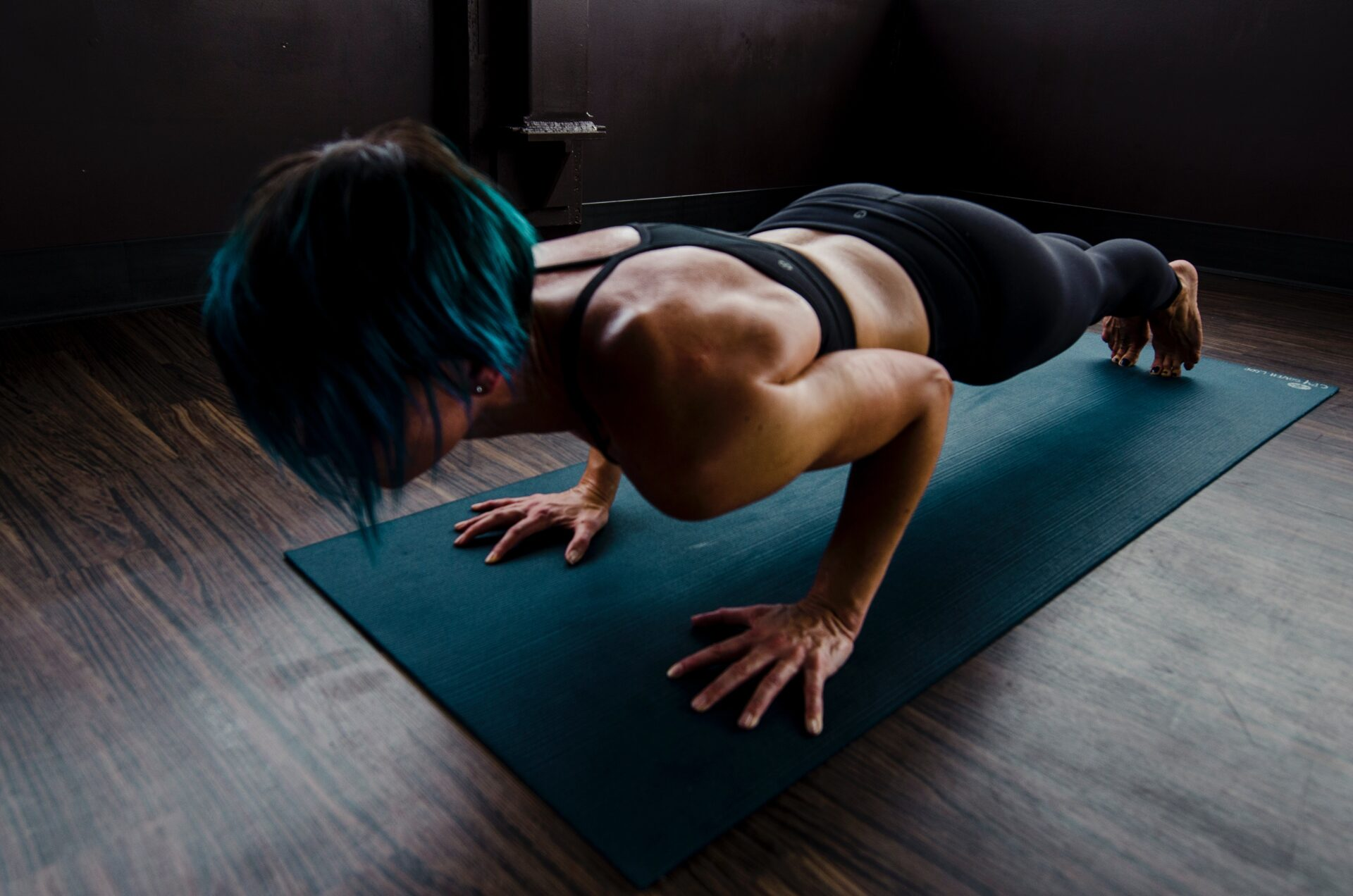 female with short blue hair planking