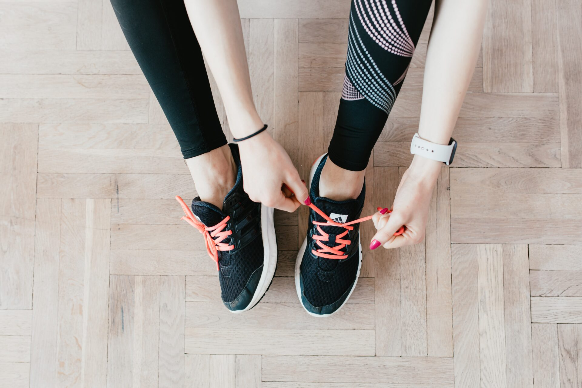 ladies legs and hands tying up trainers