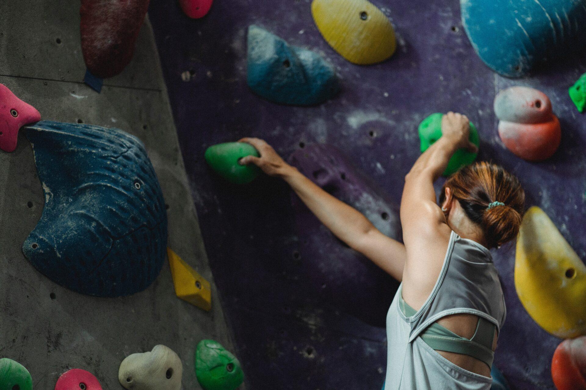 close up of a girl climbing a rock climbing wall