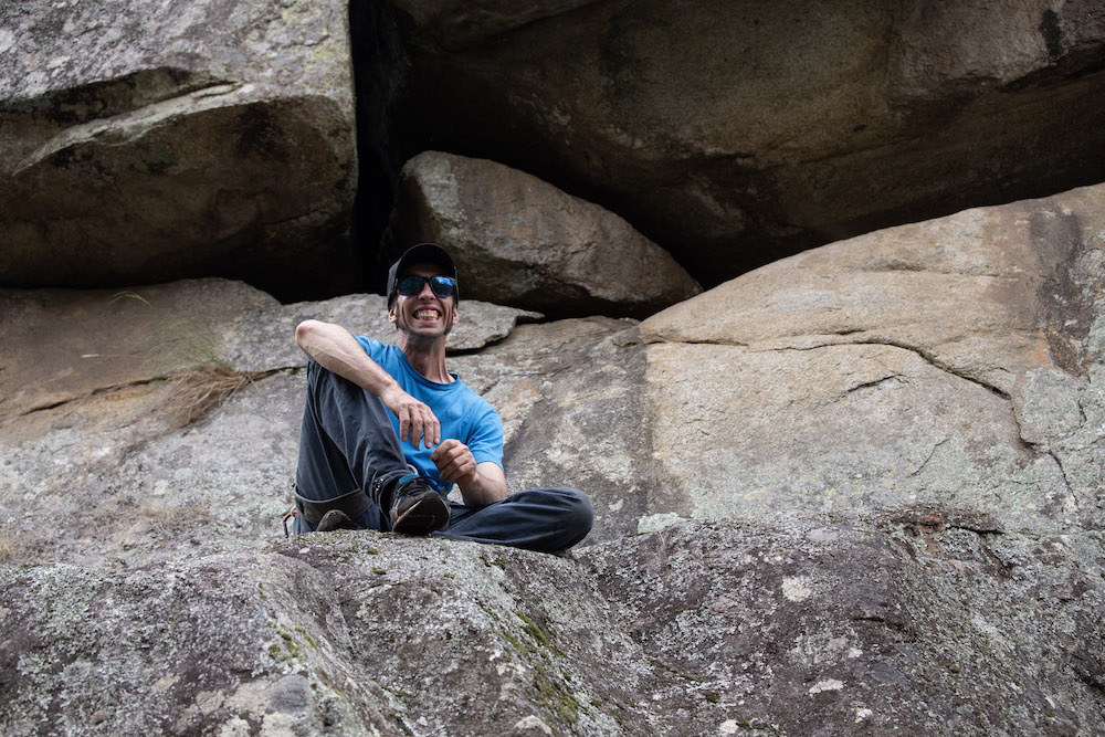 Thor Burey, UNE Outdoor Adventure Club, sitting on a rock, resting from rock climbing