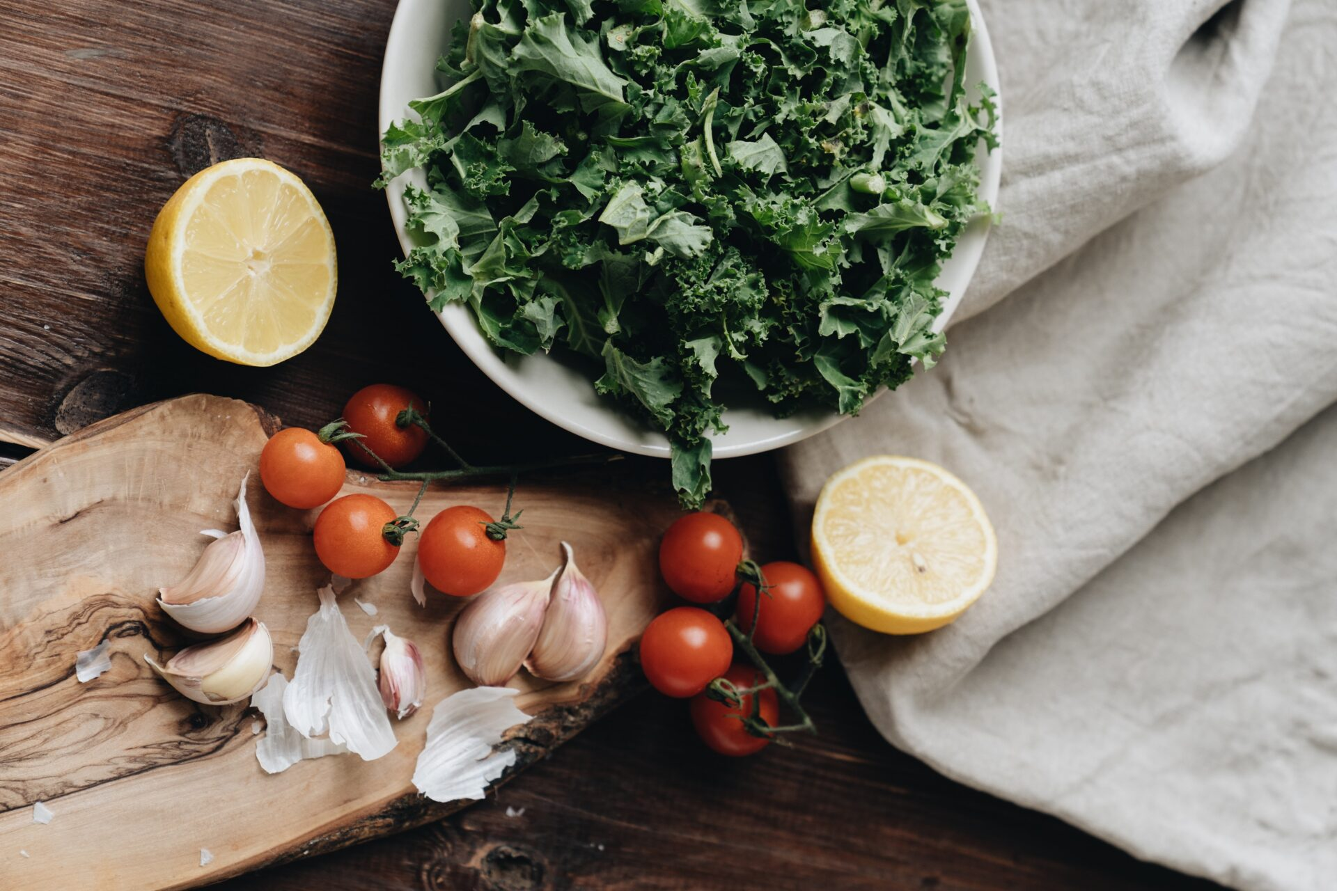 Healthy Winter vegetables including kale, lemon, cherry tomatoes, and garlic on a chopping board