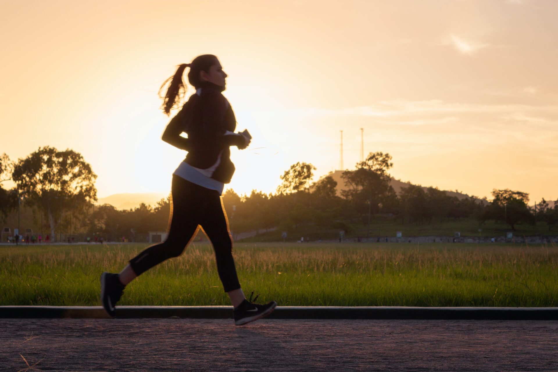 Lady running on a road at sunset