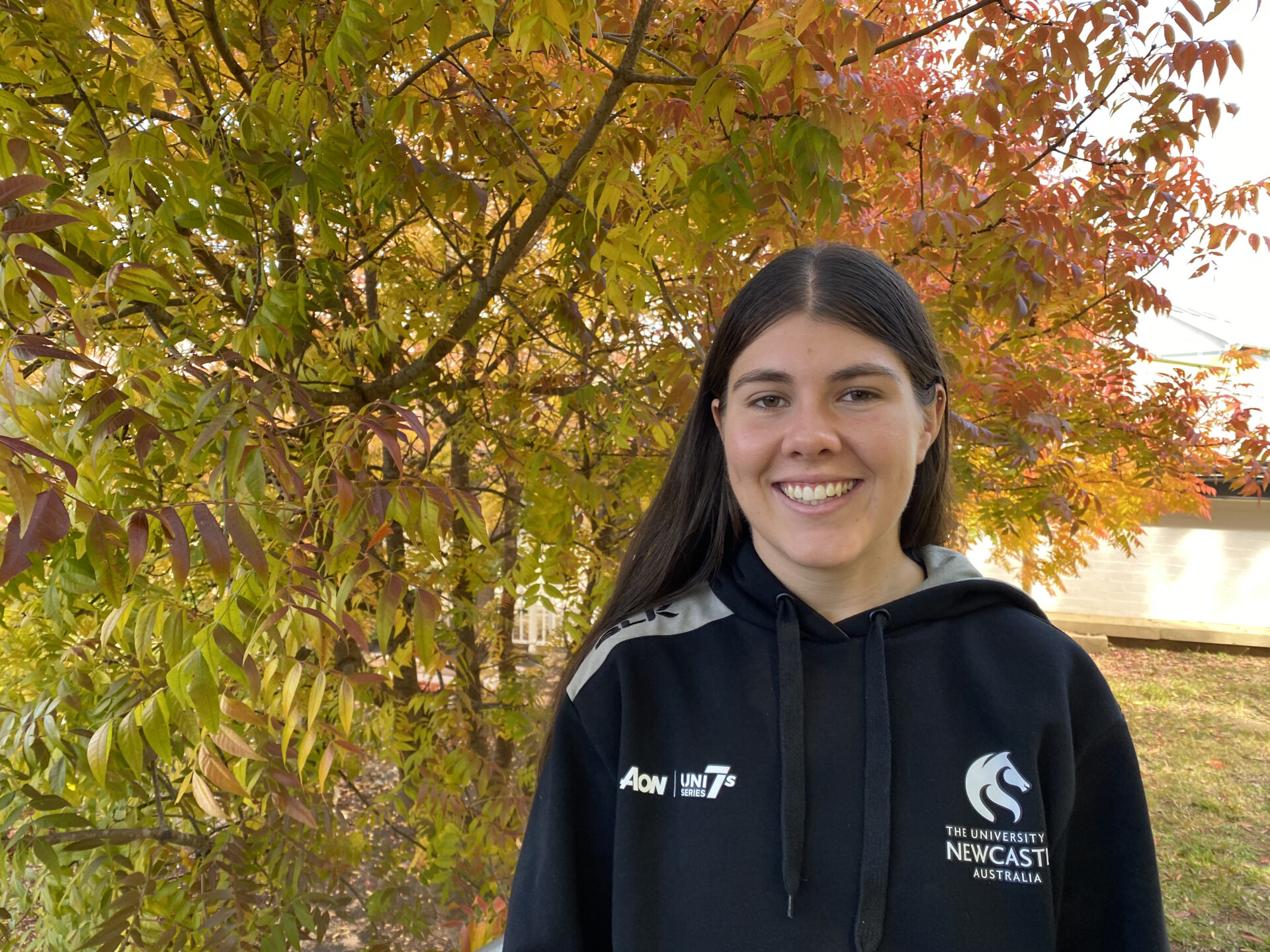 Clare Harpley, UNE Student and Elite Athlete standing in front of a tree smiling