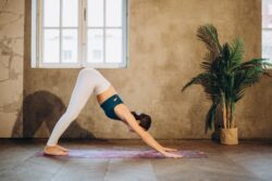 Woman in grey yoga pants and green top doing downward dog on a pink yoga mat