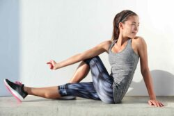 Girl with brown hair wearing grey active wear doing a form of the piriformis stretch