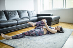 Woman Lying And Doing Half Knees To Chest Pose At Home