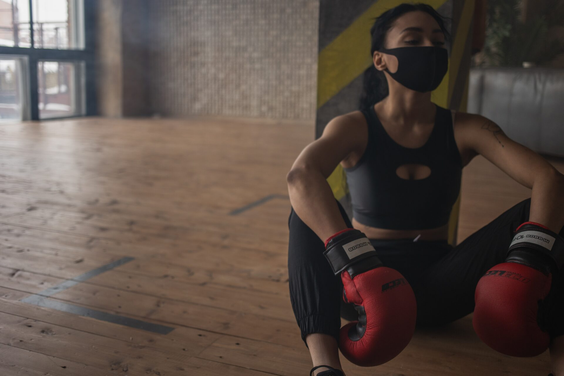 Girl in active wear and a face mask and boxing gloves, sitting down, puffed after boxing